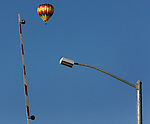 Some earthy objects point to a hot air balloon sailing over the vineyards of Napa Valley, California.