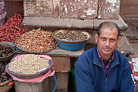 Kathmandu, Nepal.  Vendor of Dried Fish, Onions, and Peppers  Awaits Customers, Durbar Square Market.  He wears a tikka on his forehead, a red mark serving as a blessing and a symbol of Hinduism.