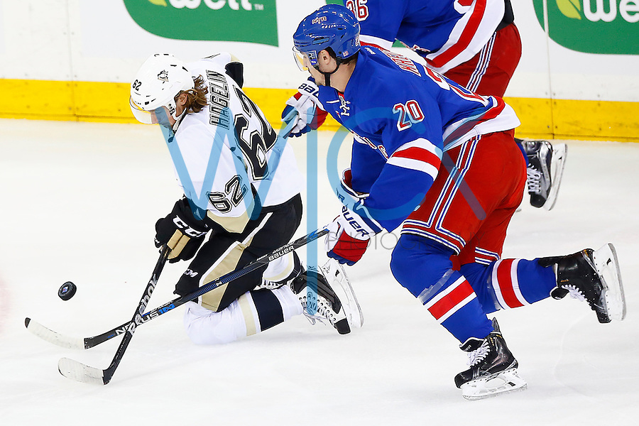 Carl Hagelin #62 of the Pittsburgh Penguins moves the puck from his knees in front of Chris Kreider #20 of the New York Rangers in the first period during game four of the first round of the Stanley Cup Playoffs at Madison Square Garden in New York City on April 21, 2016. (Photo by Jared Wickerham / DKPS)