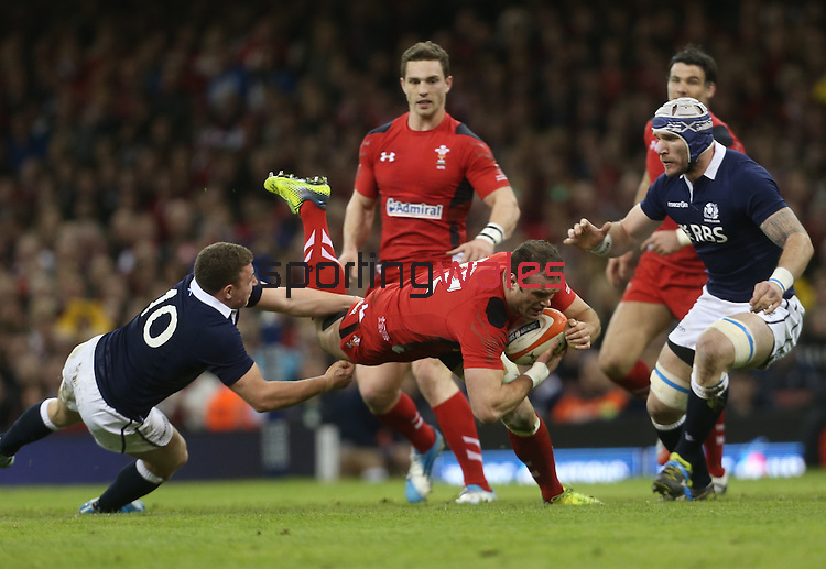 Wales centre Jamie Roberts flies past the Scottish outside half Duncan Weir.<br /> RBS 6 Nations 2014<br /> Wales v Scotland<br /> Millennium Stadium<br /> <br /> 15.03.14<br /> <br /> ©Steve Pope-SPORTINGWALES
