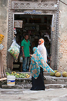 """Zanzibar, Tanzania.  Neighborhood Shop, Corner Grocery and Sundries Shop, Stone Town.  Arabian-style Door Frame, Carved Rosettes along Top Panel.  """"Phone Cards Sold Here"""", says the sign on the door frame, upper left."""