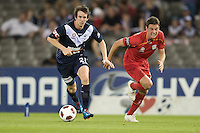 MELBOURNE, AUSTRALIA - OCTOBER 30: Fabian Barbiero of United chases Robbie Kruse of the Victory compete for the ball during the round 12 A-League match between the Melbourne Victory and Adelaide United at Etihad Stadium on October 30, 2010 in Melbourne, Australia.  (Photo by Sydney Low / Asterisk Images)