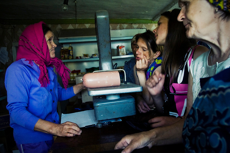 Women are weighting a piece of sausage in a local shop in Kenozero. With their salary they can't afford to do it too often