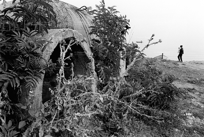 Albania. Province of Pogradec. Pogradec. A derelict bunker close to lake Ohrid 's front. Enver Hoxha (1908-1985) was for 40 years a dictator and a communist leader. He decided after the historic break with Russia in 1961 to protect his country from any invaders by investing in a massive fortification (more than a million bunkers were built over the years till 1985). © 2003 Didier Ruef