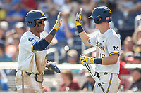 Michigan Wolverines designated hitter Jordan Nwogu (42) is greeted by teammate Jimmy Kerr (15) during Game 11 of the NCAA College World Series against the Texas Tech Red Raiders on June 21, 2019 at TD Ameritrade Park in Omaha, Nebraska. Michigan defeated Texas Tech 15-3 and is headed to the CWS Finals. (Andrew Woolley/Four Seam Images)