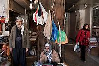A female shopper walks past street traders in Kirkuk's Rawi Mawa market. .