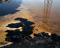 An electricity pylon is reflected in a pool of oil and water in the Caspian Sea.