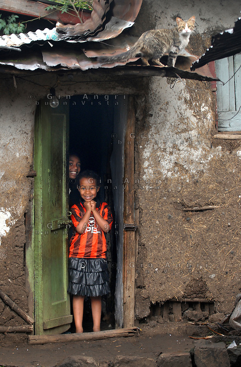 addis abeba, ethiopia, bambina con maglietta del Milan e gatto sul tetto. Child with Milan footbal club t-shirt, and cat