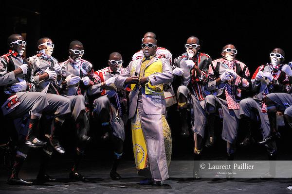 """Danse et théâtre musical - Afrique du Sud..Palais Royal (1er)..16, 17 et 18 juillet à 22h..Tarif 1..Robyn Orlin..Walking next to our shoes...intoxicated by strawberries and cream, we..enter continents without knocking.....Création 2009 - Première à Paris..Chorégraphie : Robyn Orlin..avec : Nhlanhla Mahlangu, Dudu Yende, Vusumuzi Kunene, Thulani Zwane..et la chorale PHUPHUMA LOVE MINUS..Busani Majozi, Jabulani Mcunu, Mbongeleni Ngidi, Mbuyiseleni Myeza, Mlungiseleni Majozi, Mqapheleni..Ngidi, Saziso Mvelase, Siyabonga Manyoni, S'yabonga Majozi..Assistant à la chorégraphie : Nhlanhla Mahlangu..Costumes : Birgit Neppl..Lumières : Robyn Orlin/Denis Hutchinson..Vidéo : Philippe Lainé..Conseiller musical : Boris Vukafovic..Coordination : Daniela Goeller..Comment ça va en Afrique du Sud ? Réponse de l'iconoclaste Robyn Orlin : """"Nous ne sommes pas..pauvres... Nous continuons à faire la fête et à exprimer nos idées."""" Petite plongée musicale dans les..rues de Johannesburg, entre élégance et dénuement...En zoulou, """"marcher à côté de ses pompes"""", ce n'est pas être perdu mais être pauvre. Au début du XXe siècle,..les travailleurs immigrés à la ville étaient parqués dans des hôtels - lorsqu'ils rentraient le soir, ils devaient se..déchausser et marcher sur la pointe des pieds pour faire le moins de bruit possible. De là sont nés un verbe qui..signifie """"piétiner soigneusement"""" et un style de chant a cappella teinté de gospel, l'isicathamiya. Un blues à la..sud-africaine qui se pratique aujourd'hui dans les rues des grandes villes sous forme de concours d'éloquence..et d'élégance. Cette tradition, Robyn Orlin la revisite avec son humour corrosif, et elle nous donne au passage,..sans pathos ni concessions, quelques nouvelles de l'Afrique du Sud post-apartheid. Avec les dix chanteurs du..choeur traditionnel Phuphuma Love Minus, une chanteuse lyrique, deux danseurs et un swanker - très chic..sapeur à la mode de Durban.....© Laurent Paillier/ photosdedanse.com"""