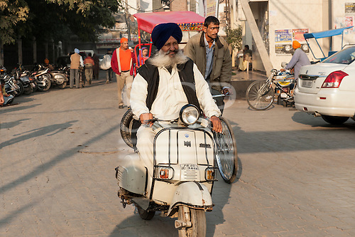 Amritsar, Punjab, India. Elderly Sikh man with flowing white moustache riding a Bajaj Vespa motor scooter wearing spotless white shirt and trousers.