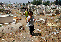 """Gaza.June.22.2008.Ahmad Jilo  a four-year-old  Playing among graves, he was born and grew up in the cemetery , """"he don't go out from this place and he don't fear from the tombs because we live and play here.""""The family was drove out from their original village in the 1948 when Jews  forced thousands of Palestinians to migrate, establishing the State of Israe.June.22.2008l.""""photo by Fady Adwan/propaimages"""""""