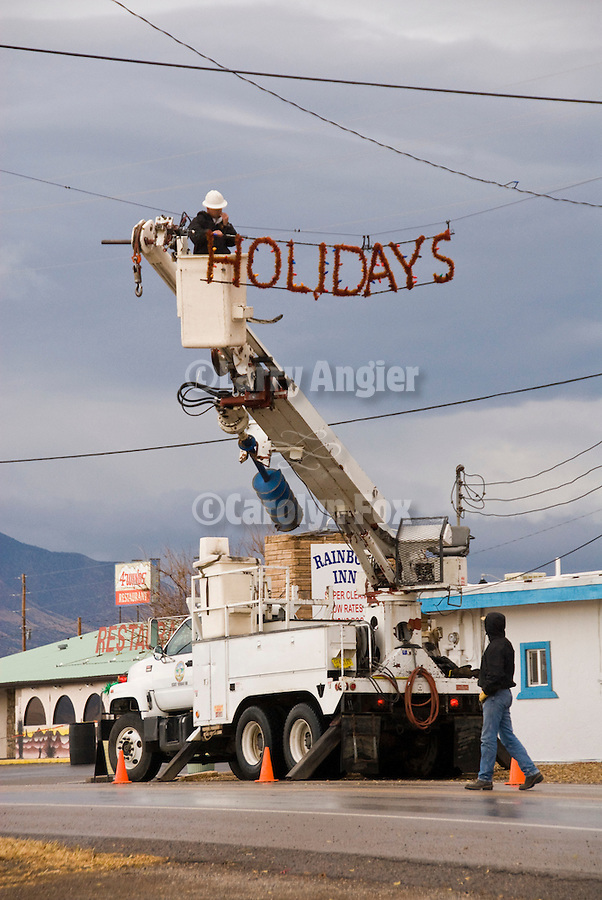 Happy Holidays sign being hung over US 54 and put up by the local electrical co-op company, Corizozo, New Mex.