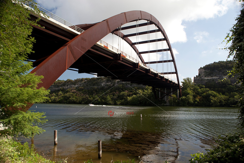 360 Bridge stands as boaters and skiers skim across the crystal clear waters of lake austin, Texas, USA