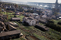Houses and farm plots cover the ground underneath the Yangtze River Bridge No. 1, one of the longest bridges in China, in the northwestern outskirts of Nanjing, China.