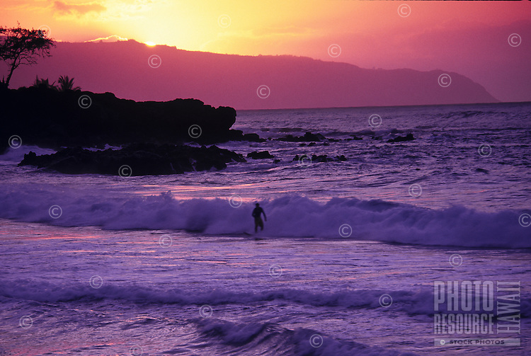 Winter sunset over Waimea Bay with surfers surfing, island of Oahu