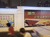 China. Shanghai. Downtown. Town center. A woman and a man pulls a cart with a rope on the concrete road and passes near new modern building under construction. Billboard of  the Expo 2010 Shanghai China on the wall. World Expo. Drawing on the China Pavilion. Haiba is the name of the mascot of World Expo 2010 Shanghai China. Hai Bao means the treasure of the sea. The name of Hai Bao is easy to remember, echoes with the color of its body and is a typical lucky name in Chinese tradition. Hai Bao is the good well ambassador of Shanghai Expo and is embracing friends from all over the world with his arms and confident smile. Night scene. 26.06.10 © 2010 Didier Ruef