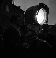 """Tournage du film """"La Bourse ou la Vie"""" de Jean Pierre Mocky, dans le quartier de St Sernin, Tououse, France, novembre 1965<br /> <br /> 2 novembre 1965. plan 3/4 de profil sur la gauche du réalisateur Jean-Pierre Mocky, donnant dans la pénombre des indications à ses techniciens lors du tournage<br /> <br /> PHOTO:  Fonds André Cros,"""