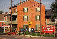Old red brick building in downtown Strasburg, Old Village Store sign in foreground. Strasburg Pennsylvania USA Lancaster County.