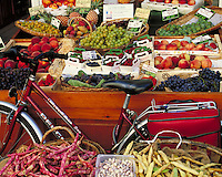 Colorful produce in trays and baskets displayed with prices outside Le Fruitier shop. Shiny woman's bicycle leans against one table. L'Isle sur, la Sorgue Provence France.