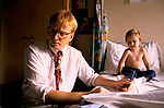 NHS 1980s Doctor Phil Hammond with child asthma attack patient. at the Royal United Hospital Bath Hospital Somerset 1989 UK