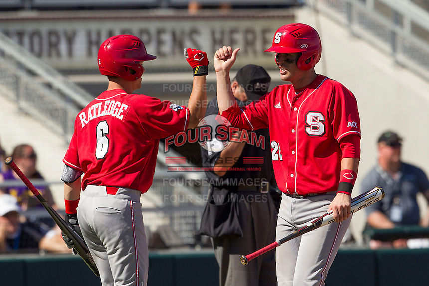 North Carolina State second baseman Logan Ratledge (6) is greet by teammate Jake Armstrong (23) after he scored during Game 3 of the 2013 Men's College World Series between the North Carolina State Wolfpack and North Carolina Tar Heels at TD Ameritrade Park on June 16, 2013 in Omaha, Nebraska. The Wolfpack defeated the Tar Heels 8-1. (Andrew Woolley/Four Seam Images)