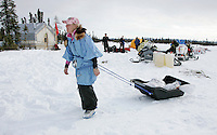 Dee Dee Jonrowe hauls her food bags to her parkign spot on Thursday at the Cripple checkpoint