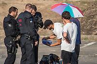 """Nach den pogromartigen Ausschreitungen gegen eine Fluechtlinsunterkunft im saechschen Heidenau am Freitag den 21. August 2015 durch Anwohnerinnen der Ortschaft, kamen am Samstag de 22. August 2015 ca. 250 Menschen in die Ortschaft um ihre Solidaritaet mit den Gefluechteten zu zeigen.<br /> Am Vorabend hatten Rassisten, Nazis und Hooligans sich zum Teil Strassenschlachten mit der Polizei geliefert um zu verhindern, dass Fluechtlinge in einen umgebauten Baumarkt einziehen. Ueber 30 Polizisten wurden dabei verletzt.<br /> Bis in die Abendstunden des 22. August blieb es trotz spuerbarer Anspannung um die Unterkunft ruhig. Im Laufe des Tages wurden immer wieder Gefluechtete mit Reisebussen gebracht was von den wartenenden Heidenauern mit Buh-Rufen begleitet wurde. Vereinzelt wurde auch """"Sieg Heil"""" gerufen, was die Polizei jedoch nicht verfolgte.<br /> Kurz vor 23 Uhr griffen Nazis und Hooligans dann wie am Vorabend die Polizei mit Steinen, Flaschen, Feuerwerkskoerpern und Baustellenmaterial an. Die Polizei mussten mehrfach den Rueckzug antreten, scheuchte den Mob dann von der Fluechtlingsunterkunft weg. Dabei wurden auch wieder Traenengasgranaten verschossen. Mindestens ein Nazi wurde festgenommen.<br /> Im Bild: Die Polizei kontrolliert akribisch die Teilnehmer der antirassistischen Kundgebung. Selbst Aepfel und belegte Brote werden inspiziert.<br /> 22.8.2015, Heidenau<br /> Copyright: Christian-Ditsch.de<br /> [Inhaltsveraendernde Manipulation des Fotos nur nach ausdruecklicher Genehmigung des Fotografen. Vereinbarungen ueber Abtretung von Persoenlichkeitsrechten/Model Release der abgebildeten Person/Personen liegen nicht vor. NO MODEL RELEASE! Nur fuer Redaktionelle Zwecke. Don't publish without copyright Christian-Ditsch.de, Veroeffentlichung nur mit Fotografennennung, sowie gegen Honorar, MwSt. und Beleg. Konto: I N G - D i B a, IBAN DE58500105175400192269, BIC INGDDEFFXXX, Kontakt: post@christian-ditsch.de<br /> Bei der Bearbeitung der Dateiinformationen darf die """