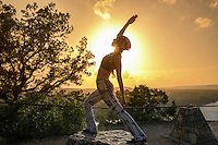 Young woman doing beautiful yoga pose, sunset silhouette on Mount Bonnell over blue sky and clouds with sunbeam sunlight background, Austin, Texas. Healthy lifestyle successful fitness exercise concept.