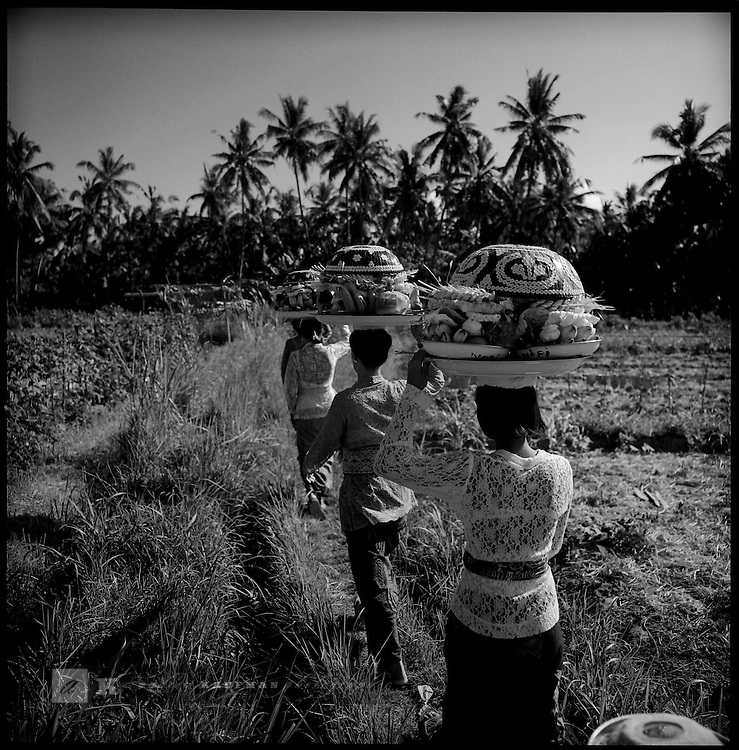 Women are walking down the trail to the beach to make an offering. Most rituals are held to bring harmony between life on earth and the universe. Harmony is an important concept in Balinese thinking. Balinese belief harmony should be maintained between themselves and their creator, between themselves, and between themselves and their surroundings.