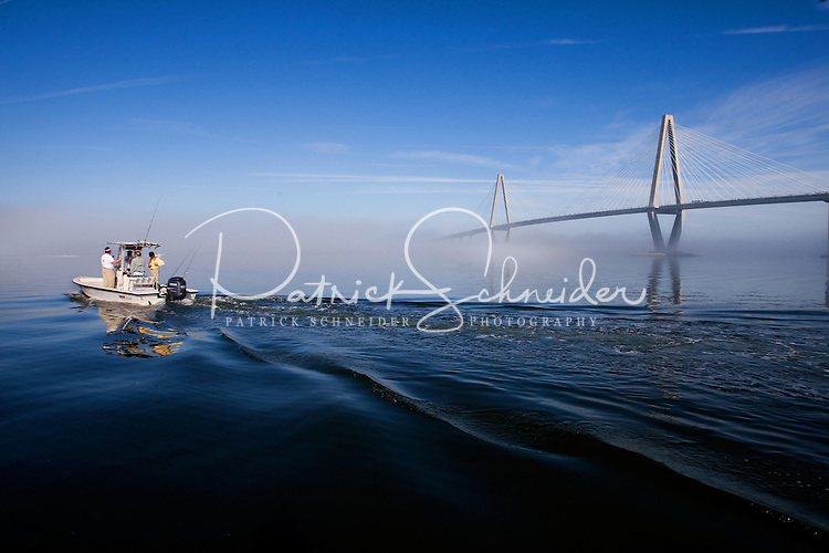 A boat of fisherman make their way out into the Cooper River as the Cooper River Bridge is in the background in Charleston, SC.