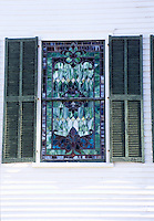 Exterior of Southern Baptist church with stained glass window and painted shutters