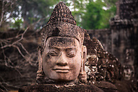 Buddha head with blurred ruins and jungle background in the ancient UNESCO heritage Khmer Angkor Wat temple, Siem Reap, Cambodia Southeast Asia