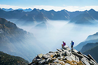 Hikers on the the Via Alta Via Maggia, a difficult week long trek from Locarno to Broglio, Switzerland as morning mist drifts through the mountains.