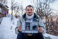 Elvis Causevic with a photograph taken 25 years earlier of a six year old Elvis playing on a gun. <br /> <br /> In 1992 while volunteering at the Varazdin refugee camp Panos photographer Bjoern Steinz met and became close to Elvis, a Bosnian Muslim refugee, and his family. They shared the hardships of camp life together which Steinz documented. While the prints were archived for many years two of the images always returned to Bjoern's thoughts. The image of Elvis playing on a gun was one of those pictures and 25 years later he set out to try and find out what had happened to Elvis and his family in the intervening years. Modern social media made the task surprisingly easy and they were reunited in Hadzici where Elvis now lives with his family.