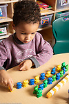Education preschool 4 year olds  boy sorting colored plastic cubes into a pattern by color, and additionally sorting colored bears into a similar pattern