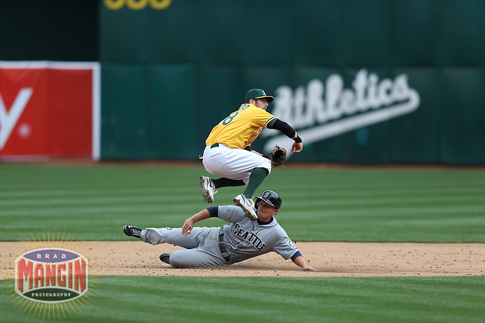 OAKLAND, CA - APRIL 4:  Eric Sogard #28 of the Oakland Athletics turns a double play at second base during the game against the Seattle Mariners at O.co Coliseum on April 4, 2013 in Oakland, California. Photo by Brad Mangin