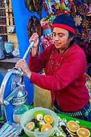 Chichicastenango, Guatemala.  Juice Vendor in the Market Squeezing Oranges.