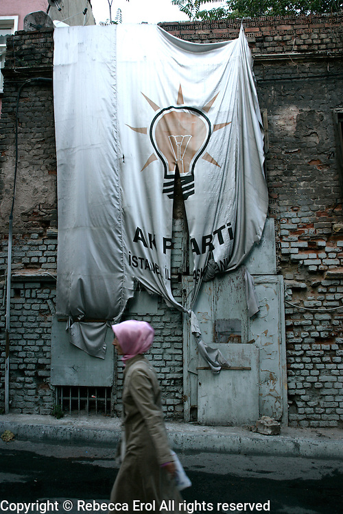 Turkish woman in a headscarf walking past tattered banner for the AK Party, Istanbul, Turkey