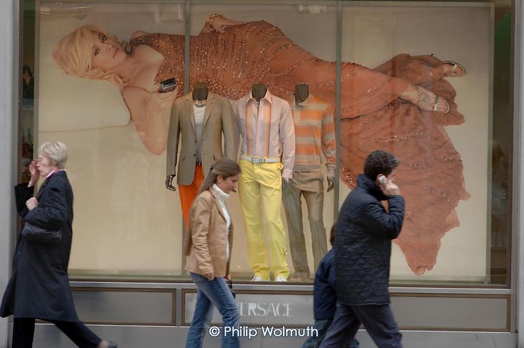 Shoppers walk past the Versace store in Bond Street, London.