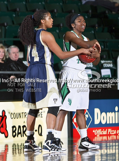 Florida International University Panthers guard/forward Rakia Rodgers (14) and North Texas Mean Green guard Brittney Hudson (5) fight for the ball in the NCAA Womens basketball game between the Florida International University Panthers and the University of North Texas Mean Green at the North Texas Coliseum,the Super Pit, in Denton, Texas. UNT defeated FIU 76 to 69