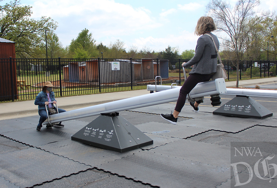 Edna Stanley (right) gets airborne as she and Dora Poage play on the Impulse seesaws installation at the Amazeum.<br /> (NWA Democrat-Gazette/Carin Schoppmeyer)
