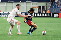 FOXBOROUGH, MA - MAY 22: Carles Gil #22 of New England Revolution breaks free of Thomas Edwards #7 of New York Red Bulls during a game between New York Red Bulls and New England Revolution at Gillette Stadium on May 22, 2021 in Foxborough, Massachusetts.