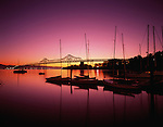 Retro Image of San Francisco downtown Oakland Bay bridge at sunrise with street lights and bridge lights, and small marina with sailboats silhouetted San Francisco, California USA