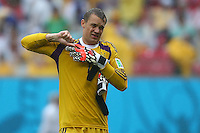 Germany goalkeeper Manuel Neuer struggles to remove his soaking wet goalkeeping gloves