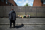 © Joel Goodman - 07973 332324 . 09/07/2017 . Bolton , UK . People bring flowers to the scene opposite the scene on Rosamond Street in Daubhill , where a fatal house fire burned through a mid-terrace house yesterday morning (Saturday 8th July 2017) . Anisha Umerji (40) her two sons Hammad (12) and Yusuf (ten) and her daughter Khadija (five) all died in the blaze. Their father Zubair (Anisha's husband) remains in hospital . Photo credit : Joel Goodman