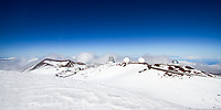 Telescopes above the clouds on top of Mauna Kea Mountain, under the snow, with a beautiful blue sky, on the Hawaii Big Island