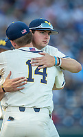 Michigan Wolverines pitcher Jeff Criswell (17) hugs teammate Ben Keizer (14) before taking on the Vanderbilt Commodores in Game 1 of the NCAA College World Series Finals on June 24, 2019 at TD Ameritrade Park in Omaha, Nebraska. Michigan defeated Vanderbilt 7-4. (Andrew Woolley/Four Seam Images)