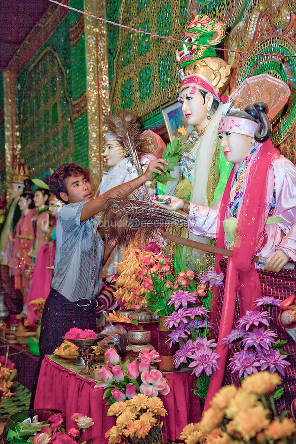 Myanmar, Burma.  Young Man Offers Gift of Marigolds to Statue Representing a Local Nat (Spirit), Mount Popa Monastery.