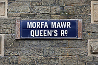 Pictured: Queen's Road (Morfa Mawr) road sign on the old Police Station in Aberystwyth, Wales, UK. Wednesday 28 August 2019<br /> Re: Opened 1866, built by the Hafod Hotel Co as the Queens Hotel; architects, Hayward and Davies; builder George Lumley of Aberystwyth. Sold in 1877 and later converted to local government use; remodelled in1950 by G R Bruce, County Architect.<br /> Detached towards N end of the Promenade, with main entrance to side elevation in Albert Place and rear elevation to Queens Road.<br /> Hotel de Ville style. Asymmetrical 3-storey attic and basement snecked rubble 13-bay W (Promenade) elevation; stepped front with mostly vermiculated dressings, stock brick voussoirs, deep entablature and cornice and cill bands; buttresses to ground floor centre. Steep pitch mansard slate roof with truncated chimney stacks. Dormers with steep overhanging roofs and casement windows; paired to left. 3-bays advanced near the right hand end and with additional storey and splayed angles to 2nd floor (with small cast-iron parapets) and 3rd floor; also to top floor) with small cast-iron parapets) and 3rd floor; also to top floor at the corner. Sash windows, some paired; anthemion panelled cast-iron window box holder across central bays.