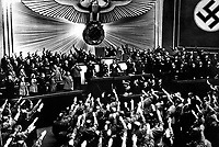 "Hitler accepts the ovation of the Reichstag after announcing the ""peaceful"" acquisition of Austria.  It set the stage to annex the Czechoslovakian Sudetenland, largely inhabited by a German-speaking population.  Berlin, March 1938.  (OWI)<br /> Exact Date Shot Unknown"
